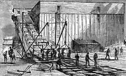 Steam-powered ice elevator for raising blocks of ice from the river level into insulated storehouses where they would be stored for summer use. Hudson River near New York.  From 'The Science Record' 1875. Engraving