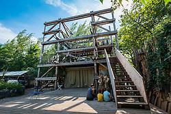 view of Die Laube or arbor, a wooden structure with platforms  at urban city community garden called Prinzessinnengarten in Kreuzberg, Berlin, Germany.
