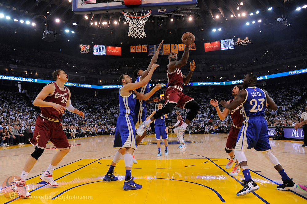 December 25, 2015; Oakland, CA, USA; Cleveland Cavaliers forward LeBron James (23, right) shoots the basketball against Golden State Warriors center Andrew Bogut (12, left) and forward Brandon Rush (4, center) during the first quarter in a NBA basketball game on Christmas at Oracle Arena. The Warriors defeated the Cavaliers 89-83.