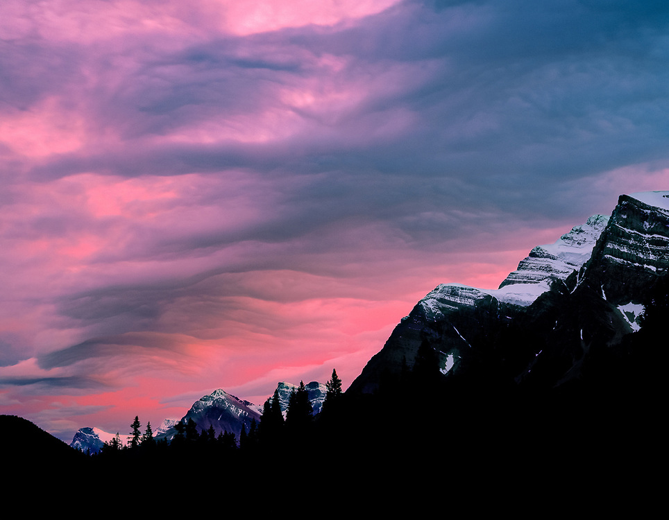 The setting sun colors the clouds above the Canadian Rockies, Alberta, Canada. ©Ric Ergenbright