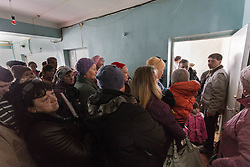 Patients , including Olga Malishenko, 23, with her son Vladislav, 2yrs 7 months (r) ,at the MSF mobile clinic in Bolshaya Vergunka, Lugansk, line up to receive their prescribed medicines.