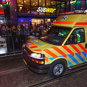 NLD/Amsterdam/20130108 - Ambulance rijdt met hoge snelheid door mensen menigte tijdens een premiere in Amsterdam