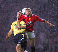 MANCHESTER, ENGLAND - MONDAY SEPTEMBER 20th 2004: Liverpool's Sami Hyypia challenges for a header with Manchester United's Alan Smith in the pouring rain during the Premiership match at Old Trafford. (Photo by David Rawcliffe/Propaganda)