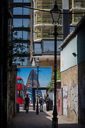 Young women talk in an graffiti alleyway opposite a London bus and a construction hoarding showing the Foster-designed Principal Tower thats under construction on Shoreditch High Street, on 10th May 2017, in London, England.