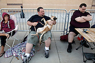 """Aaron Donoho (L) holding his dog Mina and Tony Carloni (R) wait in line at an open casting call for season 11 of """"The Biggest Loser"""" television show in Broomfield, Colorado July 17, 2010.  Over 600 people applied for a chance to be on the show and win $250,000.  REUTERS/Rick Wilking (UNITED STATES)"""