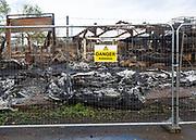 Industrial building destroyed by fire, Hatcher Components Ltd, Parham airfield, Suffolk, England, UK - Danger Asbestos sign