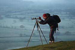 © London News Pictures. 20/01/2014. Glastonbury, UK. A photographer taking pictures of a mist covered countryside at Sunrise over Glastonbury Tor in Somerset on January 20, 2014.