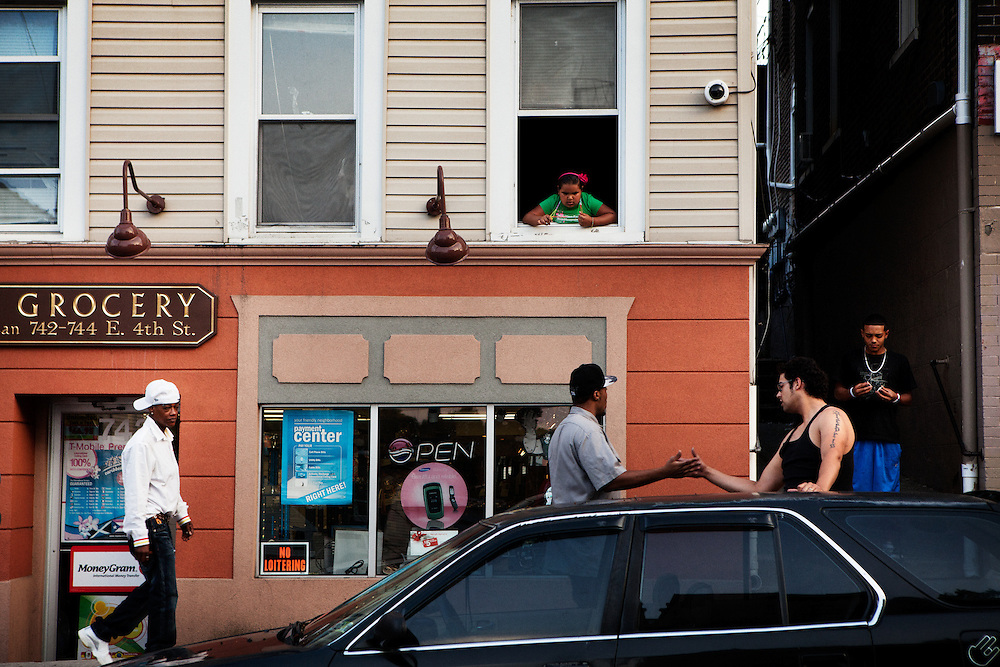 BETHLEHEM, PA – JUNE 18, 2011: Jose Marin, 22, greets a friend outside Nieves Grocery on 4th Street in Bethlehem as Angel Peres, 19, joins him from the alley. Like many Hispanics in Bethlehem, Marin immigrated to Pennsylvania's Lehigh Valley from Puerto Rico eight months earlier.<br /> <br /> As the population of second and third generation Hispanics increases dramatically in the United States, a new boldness can be sensed among Latinos in America, stretching far beyond the southern border states. Demographers in Pennsylvania say the towns of Bethlehem, Allentown and Reading are set to become majority-minority cities, where Hispanics comprise a bigger portion of the population than whites. As this minority population increases dramatically in the region, Latinos are inching closer to their own realization of the American Dream, while gradually shifting the physical and cultural landscapes of their communities.