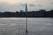 View across the River Thames towards The Shard with a metal arrow navigation pointer mirroring the shape of the building in London, United Kingdom.