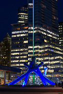 The Olympic Cauldron in Jack Poole Plaza lined up with the lights of Shaw Tower.  This was the outdoor Olympic Cauldron during the Vancouver 2010 Winter Olympics/Paralympics and is now lit during special events. Jack Poole was the head of the VANOC bid committee and was part of the team responsible for Vancouver's winning bid.  Jack Poole died in 2009 and Thurlow Plaza was renamed Jack Poole Plaza in his honour.