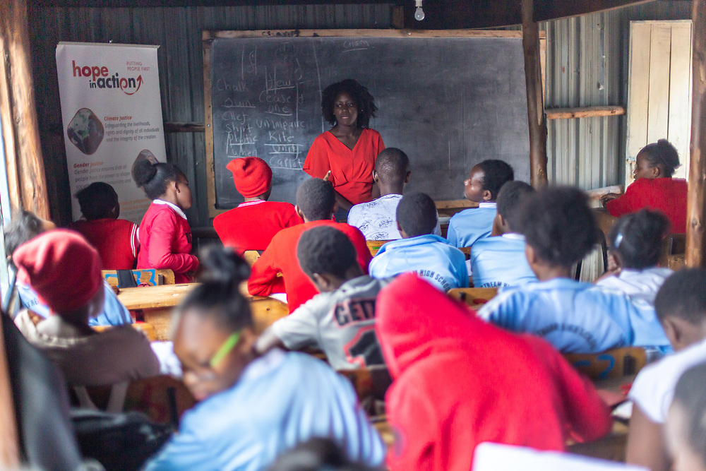 Lilian Mutheu is a mentor in the Dreams project in Nairobi, Kenya. Here she talks to a group of attentive young people in a school where the programme works. <br /> <br /> DREAMS is an acronym for Determined, Resilient, Empowered, AIDS-free, Mentored, and Safe women. The project aims to empower girls and young women between 10 and 24 years around issues including HIV prevention, contraceptive methods, health, education and social economic intervention.<br /> <br /> Lilian, who is mother, is familiar with some of the issues through her own personal experience and provides guidance and support to hundreds of young women and girls in the extensive slum of Makuru Kwa Njenga in Nairobi.