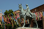Godiva statue underneath colourful bunting hanging in Broadgate in the UK City of Culture 2021 on 23rd June 2021 in Coventry, United Kingdom. The striking statue of Lady Godiva stands in the citys central square, Broadgate. Sculpted by William Reid-Dick, it was unveiled in 1949 and is one of the few statues of horses outside the capital to be listed Grade II. The UK City of Culture is a designation given to a city in the United Kingdom for a period of one year. The aim of the initiative, which is administered by the Department for Digital, Culture, Media and Sport. Coventry is a city which is under a large scale and current regeneration.