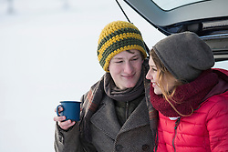 Young couple sitting on the trunk of a car with a coffee cup in winter, Bavaria, Germany