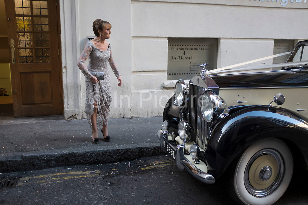 Bride arrives for her wedding in a vintage Rolls Royce, making her entrance via the 'Goods entrance' at the Connaught Rooms in central London, UK. For such a well to do wedding this dirty back street, which is normally used as a 'smokers corner' provides a huge contract to the bride in her white satin dress and guests in their expensive dresses. They all seemed very happy to be arriving through the back door though, as the atmosphere was one of laughter and smiles.