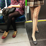 Fashinable girl wearing heart covered tights while standing on a London tube train. UK.