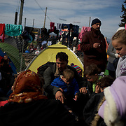 Syrian refugees sit outside their tents at the border between Greece and Macedonia in Idomeni, Greece. Around 13,000 migrants and refugees, mostly from the Middle East and African nations, are believe to be stranded here awaiting a chance to proceed their journey towards Germany and other northern European countries.