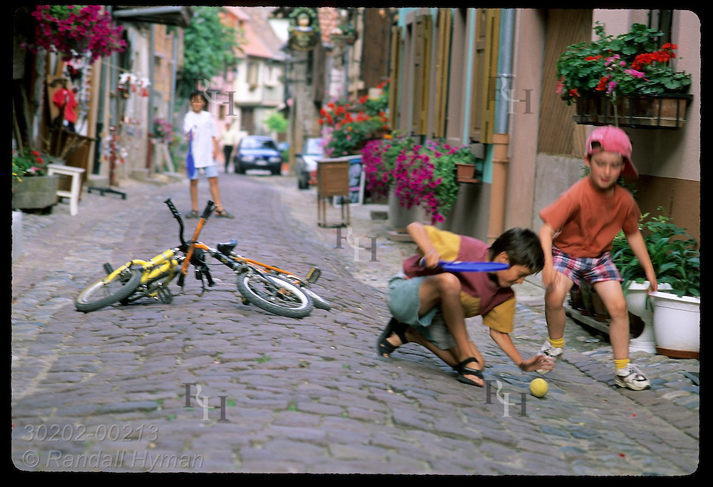 Boys scramble for ball as as they play on cobblestone street in ancient town of Eguisheim;Alsace France