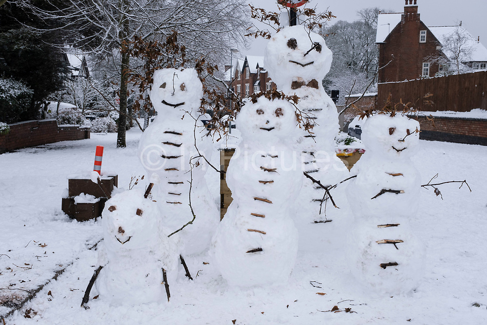 Snow man family and dog in Moseley on 24th January 2021 in Birmingham, United Kingdom. Deep snow arrived in the Midlands giving some light relief and fun during the current lockdown for people who simply enjoyed the weather.