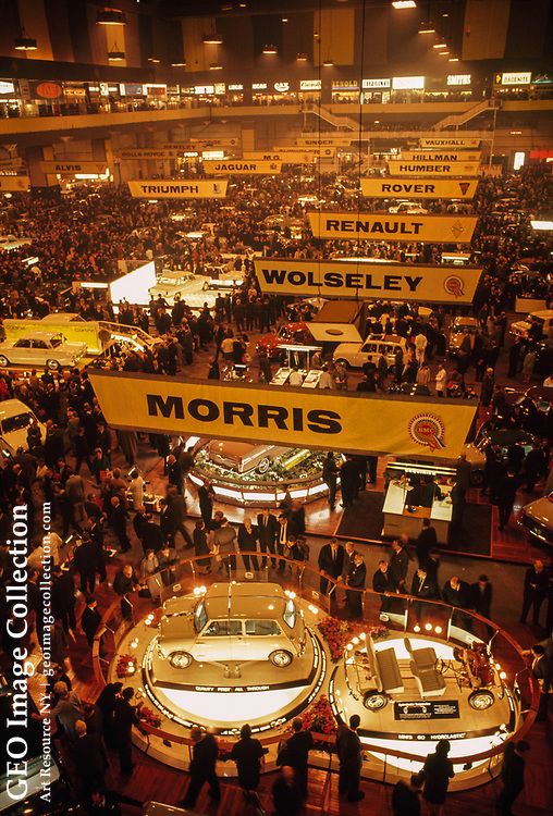 Cars, crowds, and signs fill exhibition hall during annual motor show.