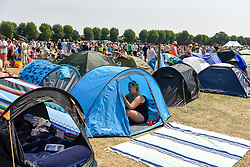 © Licensed to London News Pictures. 06/07/2018. LONDON, UK. A spectator shelters in a tent whilst queuing for day tickets in Wimbledon Park to the Wimbledon Tennis Championships.  Temperatures forecast to approach 30C mean that the majority have taken precautions to protect themselves from the sun by wearing sunglasses and sunhats.  Photo credit: Stephen Chung/LNP