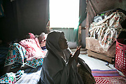Aisha A, 28, foreground, prays in her tent as her roommate, Fatima, left, lies on a mattress in an IDP camp, Maiduguri, Nigeria, April 26, 2019. Aisha was abducted by seven BH fighters in Gwoza Local Government in 2014. After she was taken to a commander's house, she was raped by him and became the fourth wife. She stayed in his home for a year and eight months, but did not get pregnant. Aisha got pregnant by an IDP man in the same camp with whom she married, and gave birth to a boy a day after this photo was taken. Also pregnant, Fatima was abducted by BH fighters when she was 15 years old. She was forced to marry a commander and gave birth to a son in 2017 whom she left in the forest. She realized she was pregnant again after escaped. Fatima gave birth to a boy ten days after this photo was taken.