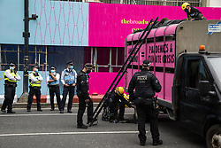 London, UK. 3rd September, 2020. Metropolitan Police and British Transport Police officers attend to animal rights activists from Animal Rebellion who had locked themselves to the top of and inside a pink slaughterhouse truck in order to block the road outside the Department of Health and Social Care. Animal Rebellion activists are protesting in solidarity with victims of the global food system and to demand that the UK transitions to a sustainable plant-based food system.