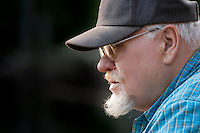 portrait of a senior man with goatee, glasses, and ballcap, concentrating on his fishing at a beaver pond in rural Kitsap County, Washington, USA