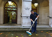© Licensed to London News Pictures. 21/11/2012. westminster, UK A worker brushes leaves away from the steps of Church House in Westminster, London for day three of the three-day Church of England General Synod. Members last night voted against ordaining women as priests.. Photo credit : Stephen Simpson/LNP