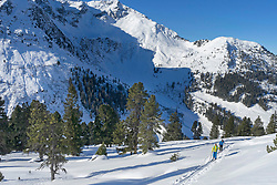 Skiers walking  on snow against mountain