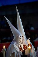 Nazarenos belonging to a Cordoba brotherhood at night during a Holy Week procession. Andalusia, Spain