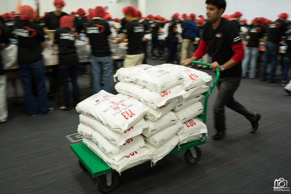 """A SanDisk employee pushes a cart loaded with bags of rice during the Stop Hunger Now Foundation's """"Mayday, Mayday"""" food-packing event at SanDisk Corporation in Milpitas, California, on May 13, 2014. (Stan Olszewski/SOSKIphoto)"""