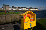 "Samaritans lifebuoy on the Claddagh, an area close to the centre of Galway city, where the Corrib River meets Galway Bay. With the words: ""A stolen Ringbuoy - A Stolen Life"" printed on the ring's box, this charity that helps the vulnerable and often suicidal hopes that people respect the presence of this installed aid to help anyone desperate enough to jump over the edge of this harbour wall and into the cold Atlantic waters. Irish people sit on the grass and old houses that front the dock are clear on this sunny day. Samaritans is a confidential emotional support service for anyone in the UK and Ireland, Scotland and Wales. Their service is available 24 hours a day for people who are experiencing feelings of distress or despair, including those that may lead to suicide."