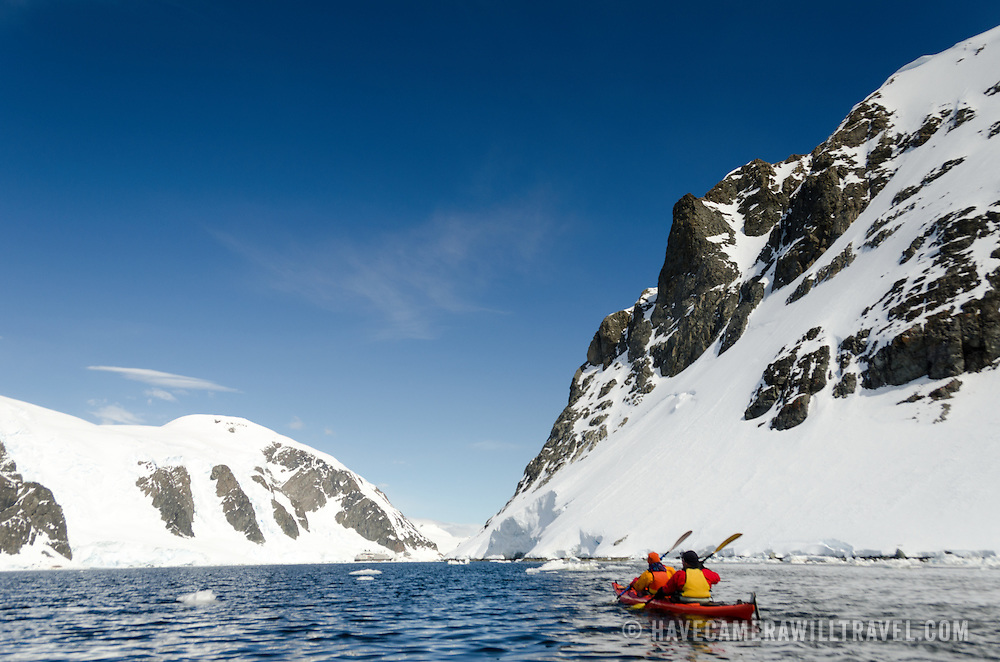 Kayakers head towards a narrow channel between steep mountain shorelines at Cuverville Island on the Antarctic Peninsula.