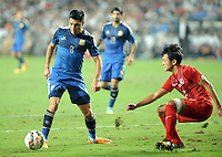 Enzo Perez of Argentina, left, challenges Cheung Kin-fung of Hong Kong during a friendly football match in Hong Kong, China, 14 October 2014.<br /> <br /> Lionel Messi needed just six minutes to make his mark in Argentina's 7-0 rout of Hong Kong in a friendly at Hong Kong Stadium on Tuesday (14 October 2014). The Barcelona star Messi scored twice after going on as a substitute for the last 30 minutes of the game to celebrate the 100th anniversary of the Hong Kong Football Association. Napoli striker Gonzalo Higuain and Benfica's Nicolas Gaitan also scored two goals each after Sevilla's Ever Banega had opened scoring in the 19th minute.
