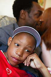 Young teenager sitting with his family; looking bored,