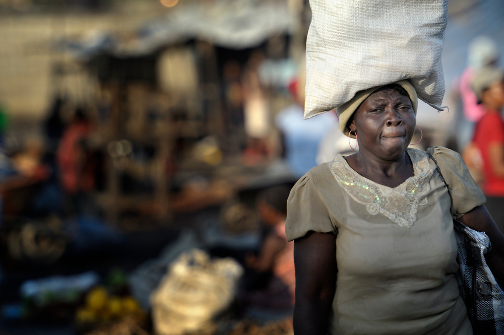 A bundle on her head, a woman walks along the street in Cite Soleil, a sprawling poor portion of Port-au-Prince, Haiti.