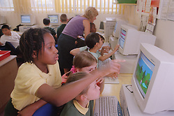 Primary school pupils learning to use computers during Information and Technology lesson,
