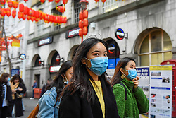 © Licensed to London News Pictures. 24/01/2020. LONDON, UK. Women wear facemasks, possibly in reaction to the outbreak of the coronavirus in Wuhan, China as red lanterns decorate Chinatown ahead of Chinese New Year, the Year of the Rat.   Photo credit: Stephen Chung/LNP