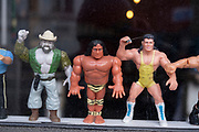 Plastic action figures of wrestling characters in the window of a bar on 5th March 2021 in London, England, United Kingdom. Some of the figures are recognisabe as from popular culture like Tarzan.
