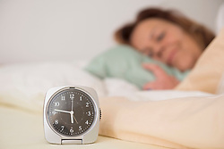 Woman asleep in bed while her alarm shows the early time at home in bedroom, Munich, Bavaria, Germany