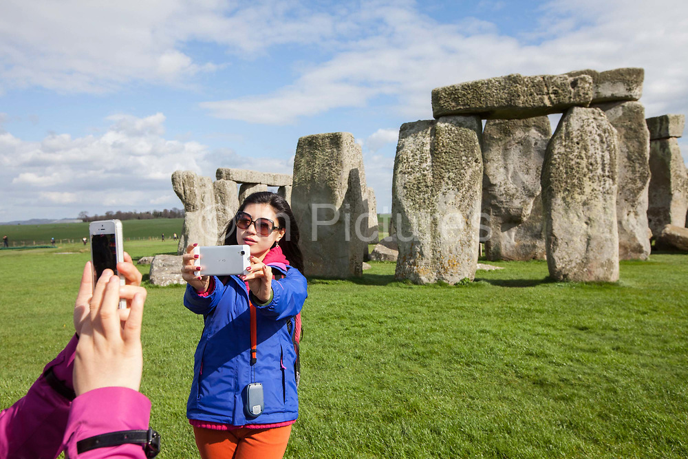 Tourists photograph themselves and the stones at the standing stone circle at Stonehenge, Wiltshire, UK. Stonehenge is a prehistoric monument and one of the most famous sites in the world. Stonehenge is the remains of a ring of standing stones set within earthworks. It is in the middle of the most dense complex of Neolithic and Bronze Age monuments in England, including several hundred burial mounds. Archaeologists believe it was built anywhere from 3000 BC to 2000 BC.