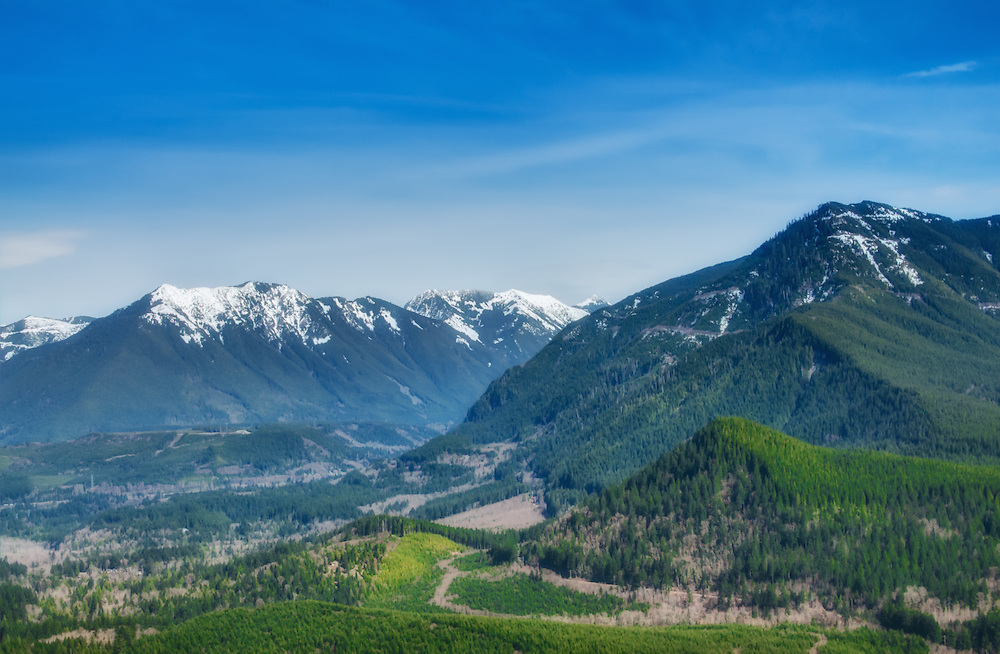 A view from atop Rattlesnake Mountain in Washington State. Maibox Peak to the left with Dirtybox Peak just to the right and behind it. On the right side is Mount Washington with Cedar Butte (the large hill) in the foreground. Between the mountains is a part of the Upper Snoqualmie Valley and the South Fork Snoqualmie River.