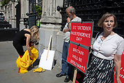 Woman climbing out of her chicken costume, part of a stunt commenting on Boris Johnson chickening out of a live TV debate beside pro Brexit protesters in Westminster as inside Parliament the Tory leadership race continues on 17th June 2019 in London, England, United Kingdom.