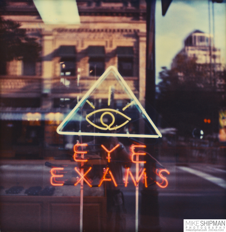 Eye Exams, eye within a triangle with words below, a neon sign in window with reflection of city street, Boise, Idaho