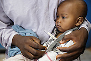 Diallo Mamadou Kalidou, 9 months old, who suffers from anemia and malaria, has his temperature taken as he sits on his father Diallo Amadou, 25, during a consultation at the Libreville health center in Man, Cote d'Ivoire on Wednesday July 24, 2013.