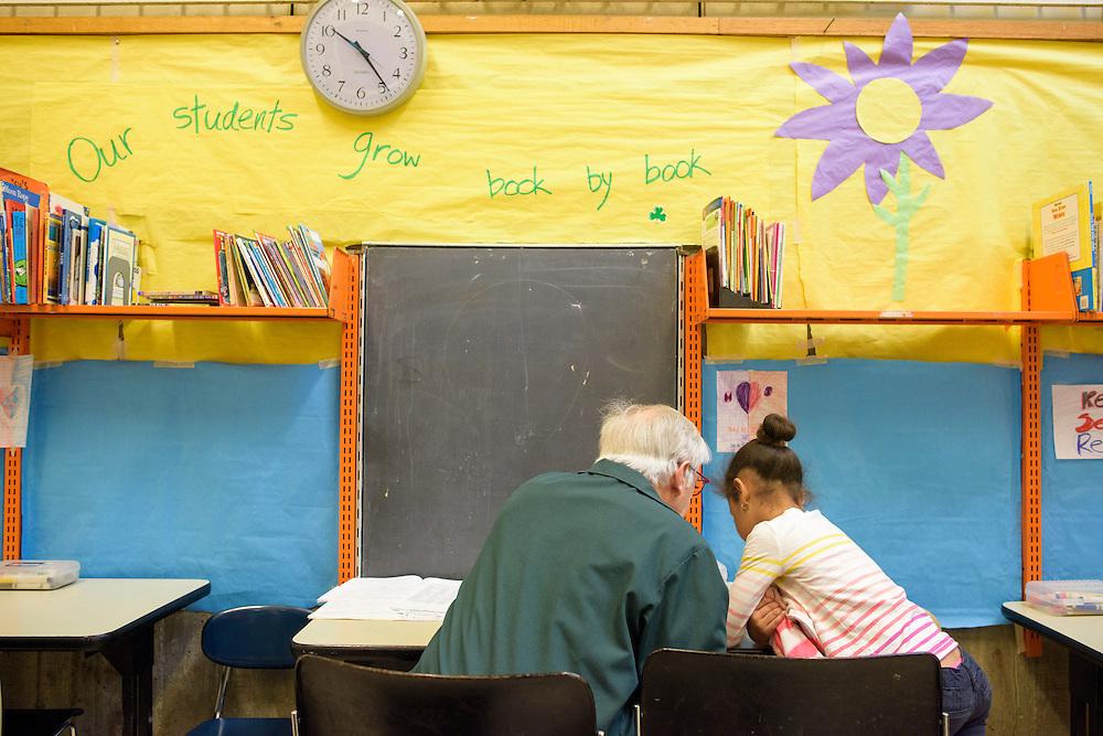 Boston, Massachusetts - May 07, 2015: AARP Experience Corps volunteer Alan Lokensgard tutors first grader Jianna Winder back to class at Blackstone Innovation School in Boston, Massachusetts.<br /> <br /> CREDIT: Matt Roth