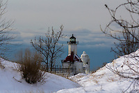 St. Joseph lighthouse covered in ice.  Nicely framed between snow covered sand dunes