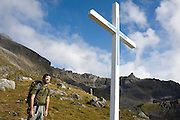 Hiker Craig Weiland encounters a white cross in the Talkeetna Mountains above Independence Mine State Historical Park, Matanuska Valley, Alaska.