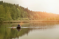Father and son traveling in boat on lake, Bavaria, Germany