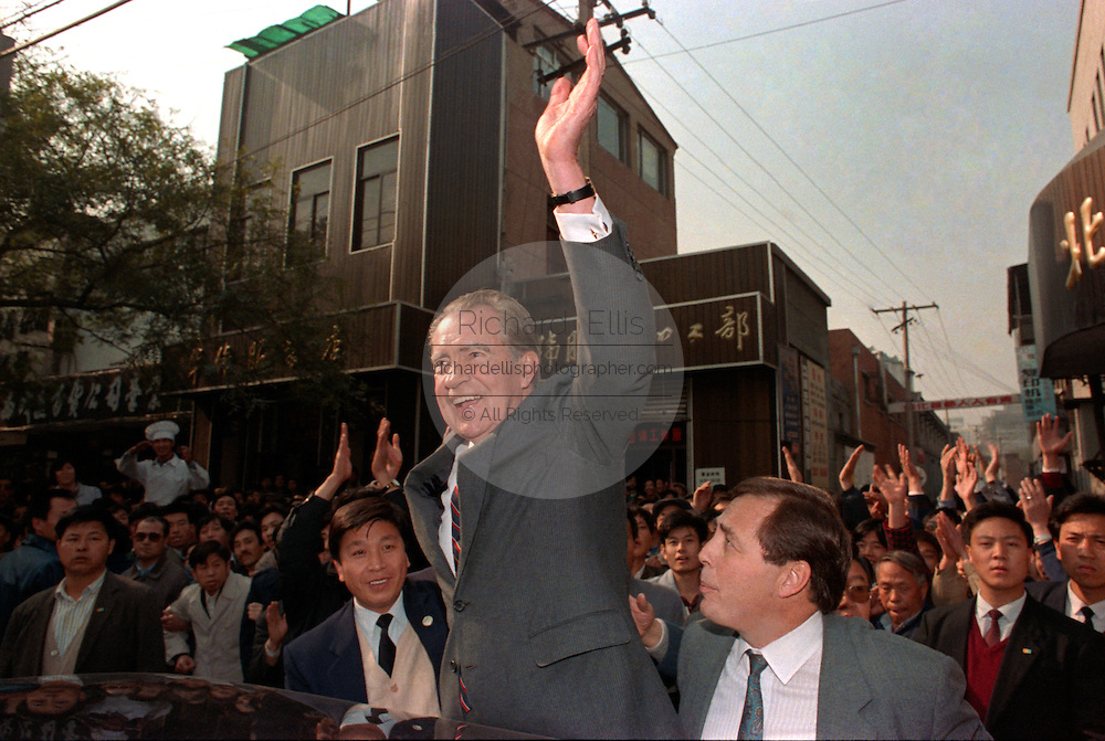 Former US President Richard M. Nixon waves to a gathered crowd during a walk around the Wangfujing Street shopping district October 30, 1989 in Beijing, China. Nixon visited as a private guest of the Chinese government.